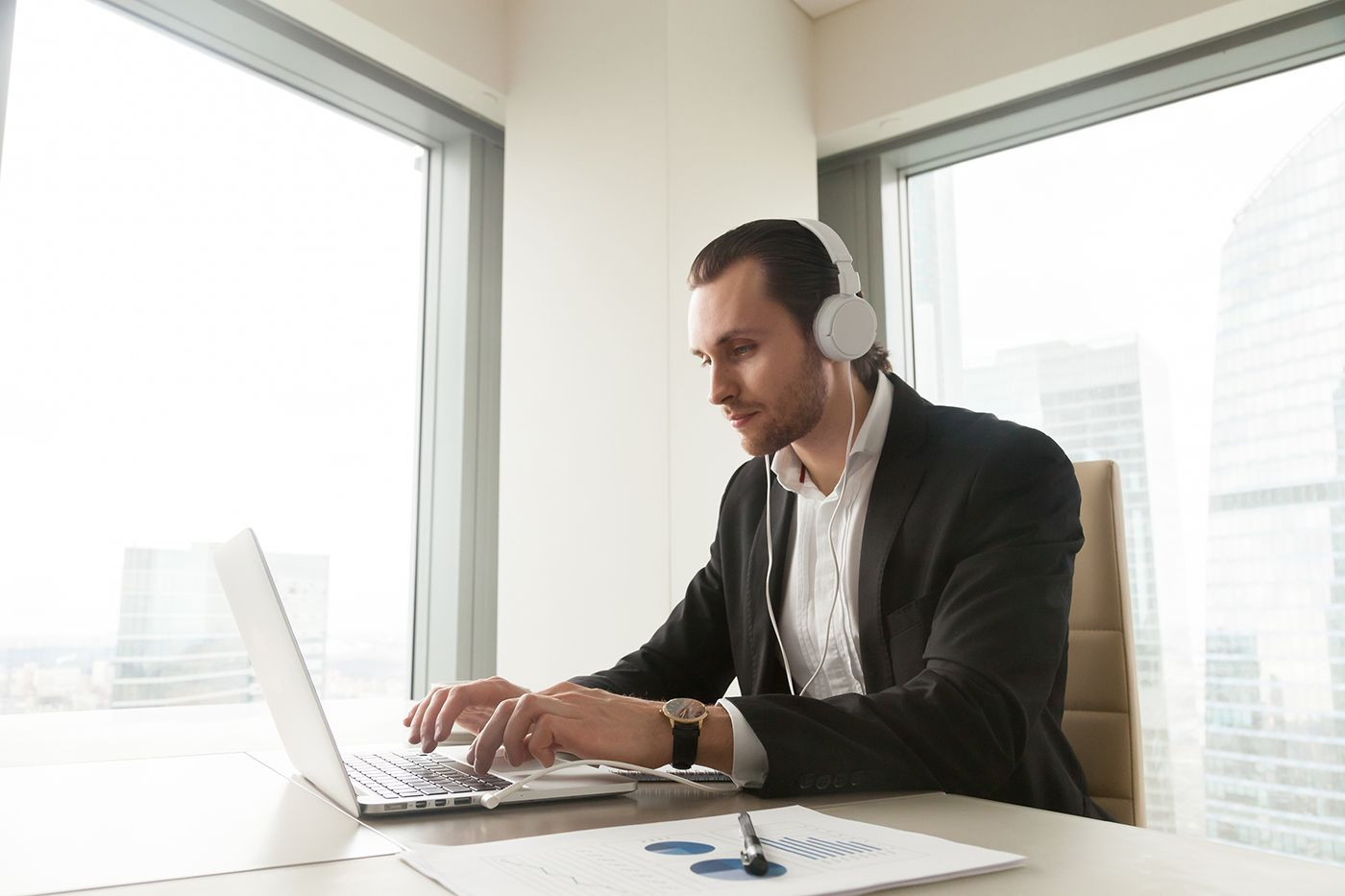 This man is following online meeting etiquette: Using headphones in a quiet, professional setting.